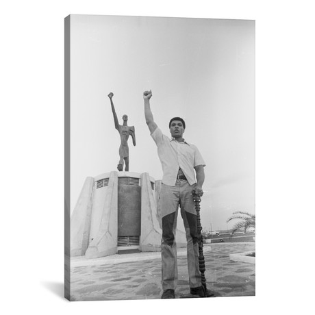 "Muhammad Ali Posing In Front Of The Le Militant Statue, Kins // Muhammad Ali Enterprises (18""W x 26""H x 0.75""D)"