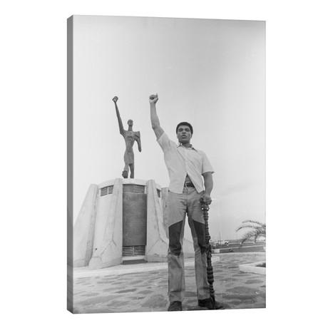 Muhammad Ali Posing In Front Of The Le Militant Statue, Kinshasa, Zaire // Muhammad Ali Enterprises